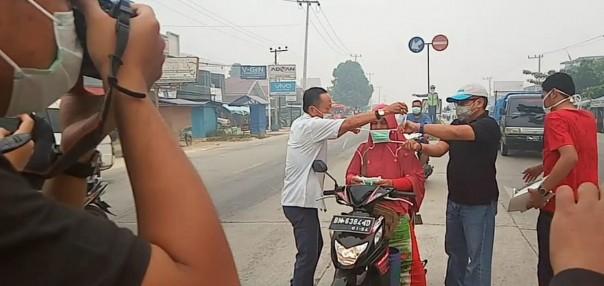 PT. Muslim Mas membagikan masker kepada pengendra di ruas jalan lintas timur, Minggu 22 September 2019. (Foto: ist)