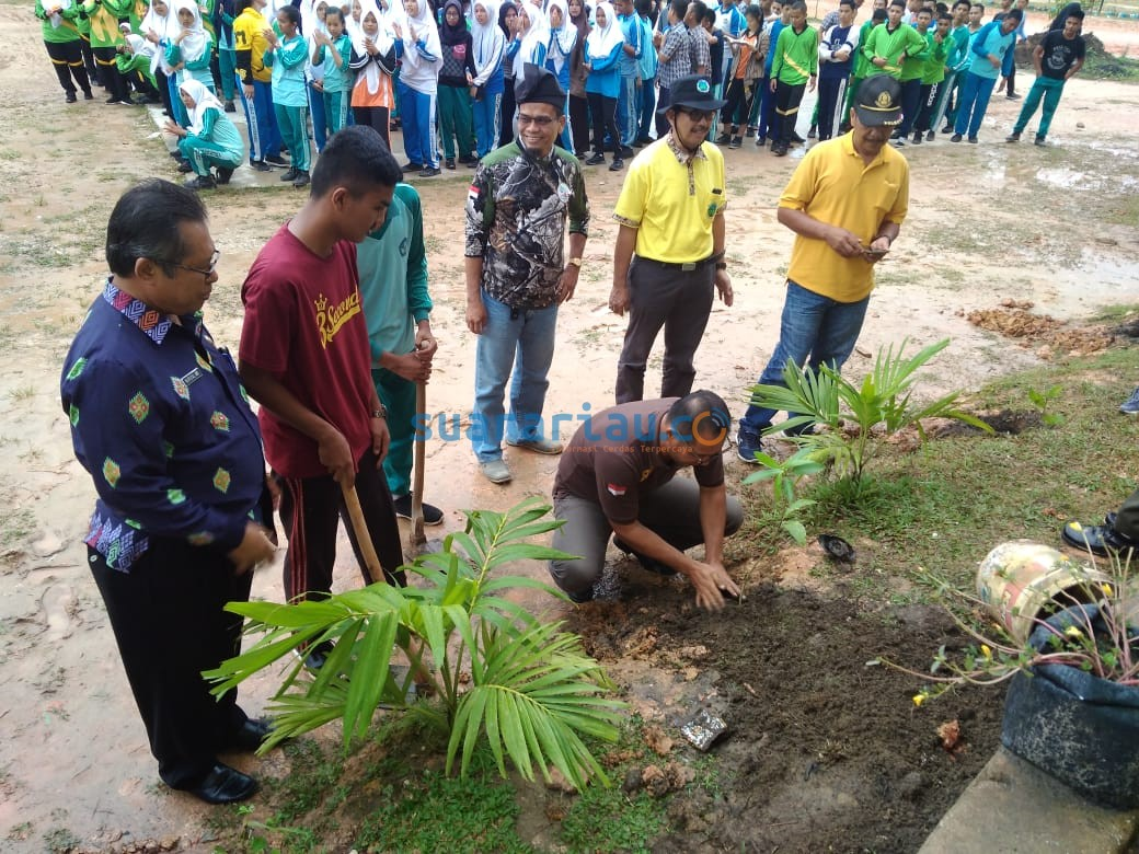 Perwakilan BBKSDA Riau, Hutajulu melakukan penanaman bibit pohon di lingkungan SMAN 16 Pekanbaru.