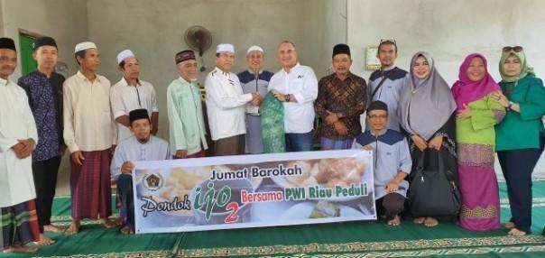 Ketua PWI Riau Zulmansyah Sekedang (enam dari kanan) menyerahkan bantuan karpet sajadah kepada Ketua Masjid Al Furqon Pranayas.