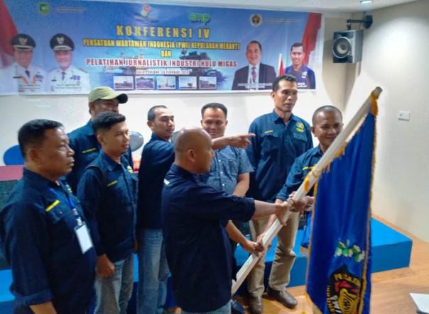 Sekretaris PWI Riau Amril Jambak menyerahkan bendera PWI kepada Syamsidir (kanan), ketua terpilih PWI Kepulauan Meranti periode 2020-2023. (Foto: Istimewa)