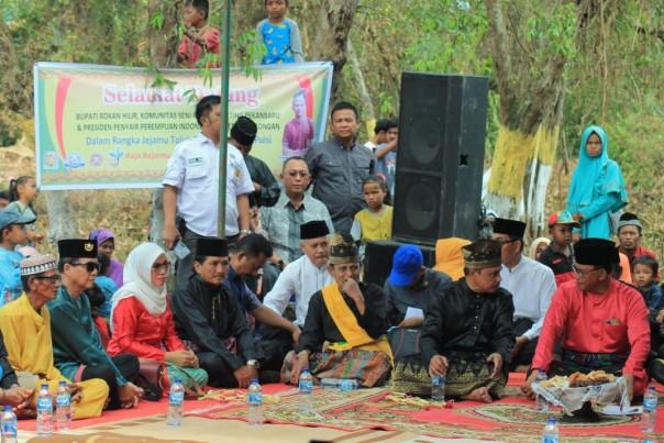Pembina Komunitas Seni Rumah Sunting dan juga Presiden Penyair Indonesia Kunni Masrohanti (baju merah) makan baselo bersama Bupati Rohil H Suyatno (baju merah) saat Jejamu Teluk Gong dan Kenduri Puisi 14, Sabtu (22/2/2020) di Kepenghuluan Raja Bejamu, Sinaboi, Rohil. (Foto: Kacamata Gober/Rumah Sunting)