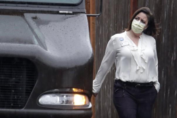 Seorang pekerja di Life Care Center di Kirkland, Washington, dekat Seattle, mengenakan topeng saat dia berjalan di dekat truk UPS selama pengiriman paket, Senin, 2 Maret 2020. Beberapa orang yang telah meninggal di negara bagian Washington dari COVID-19 coronavirus terikat dengan fasilitas perawatan jangka panjang, di mana puluhan penduduk sakit. (Foto AP)