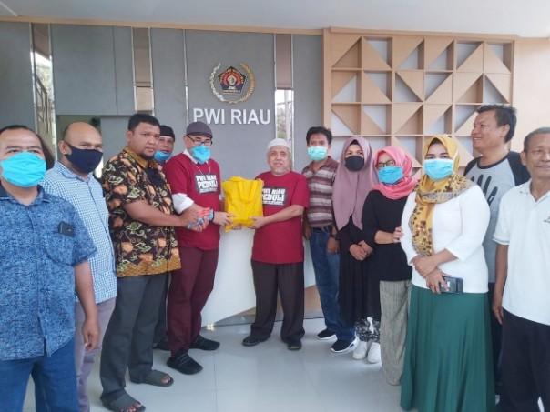 Ketua PWI Riau H Zulmansyah Sekedang menyerahkan bantuan program PWI Riau Peduli dan SPS Riau  untuk 100 reporter, yang sehari-hari meliput di lapangan./ist