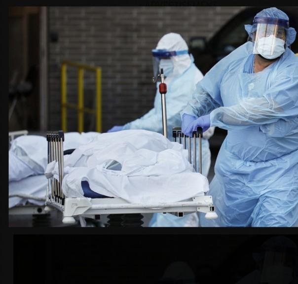 Pekerja medis yang mengenakan alat pelindung diri beroda ke trailer berpendingin yang berfungsi sebagai kamar mayat darurat di Wyckoff Heights Medical Center, Senin, 6 April 2020, di wilayah Brooklyn di New York. Coronavirus baru menyebabkan gejala ringan atau sedang bagi kebanyakan orang, tetapi untuk.(FOTO: AP)