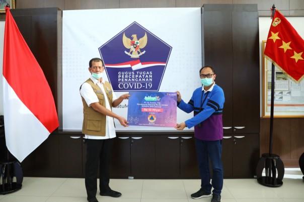 Plt Chief Teknologi Officer XL Axiata, I Gede Dharmayusa (kanan) menyerahkan donasi kepada Badan Nasional Penanggulangan Bencana (BNPB) yang diterima oleh Kepala BNPB, Doni Monardo (kiri), di Jakarta, Selasa 7 April 2020.