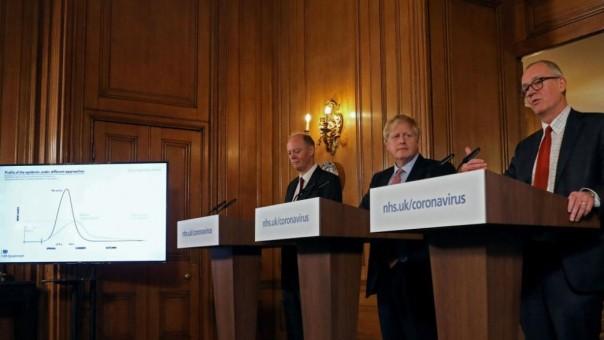 Boris Johnson, tengah, diapit oleh Kepala Medis untuk Inggris, Chris Whitty, kiri, dan Kepala Penasihat Ilmiah Patrick Vallance pada konferensi pers 12 Maret. (FOTO/CNN)
