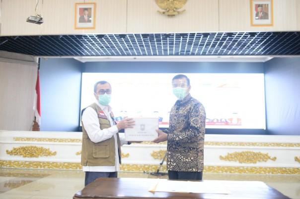 Gubernur Riau (Gubri) Syamsuar menyerahkan bantuan masker  kepada Wali Kota Pekanbaru, Firdaus./ist