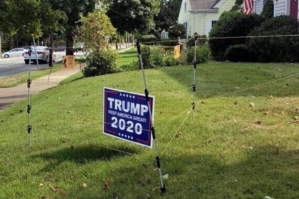 pagar listrik mengelilingi tanda kampanye untuk Presiden Donald Trump di halaman John Oliveira di New Bedford, Mass. Oliveira mengatakan dia memasang pagar untuk melindungi tandanya setelah beberapa orang dicuri dari halamannya selama musim panas. . (Foto/ AP)