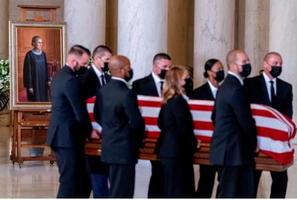 Peti jenazah Justice Ruth Bader Ginsburg yang terbungkus bendera, dibawa oleh petugas polisi Mahkamah Agung, tiba di Aula Besar di Mahkamah Agung di Washington.(reuters)