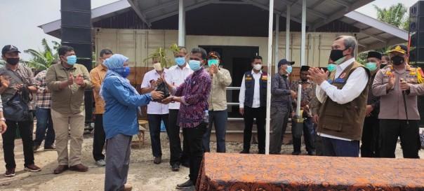 Kepala BPDASHL Indragiri Rokan, Tri Esti Indrarwati, menyerahkan KBD dari KLHK kepada kelompok masyarakat, disaksikan Gubernur Riau dan para pihak.