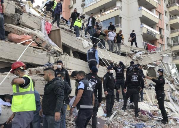 Petugas penyelamat dan warga sekitar membawa korban luka yang ditemukan di reruntuhan bangunan yang runtuh, di Izmir, Turki, Jumat, 30 Oktober 2020, setelah gempa kuat di Laut Aegea mengguncang Turki dan Yunani. Kepresidenan Manajemen Bencana dan Darurat Turki mengatakan gempa bumi pada Jumat berpusat di Laut Aegea pada kedalaman 16,5 kilometer (10,3 mil) dan tercatat pada magnitudo 6,6. (Foto/ AP )