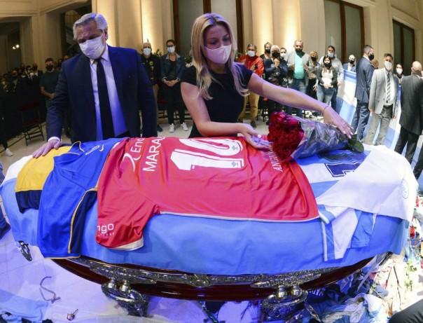 Para pelayat berpelukan saat mereka menunggu untuk melihat Diego Maradona terbaring di negara bagian di luar istana presiden di Buenos Aires, Argentina, Kamis, 26 November 2020. Hebat sepak bola Argentina yang memimpin negaranya ke Piala Dunia 1986 meninggal pada Rabu di usia 60 tahun. (Foto AP)