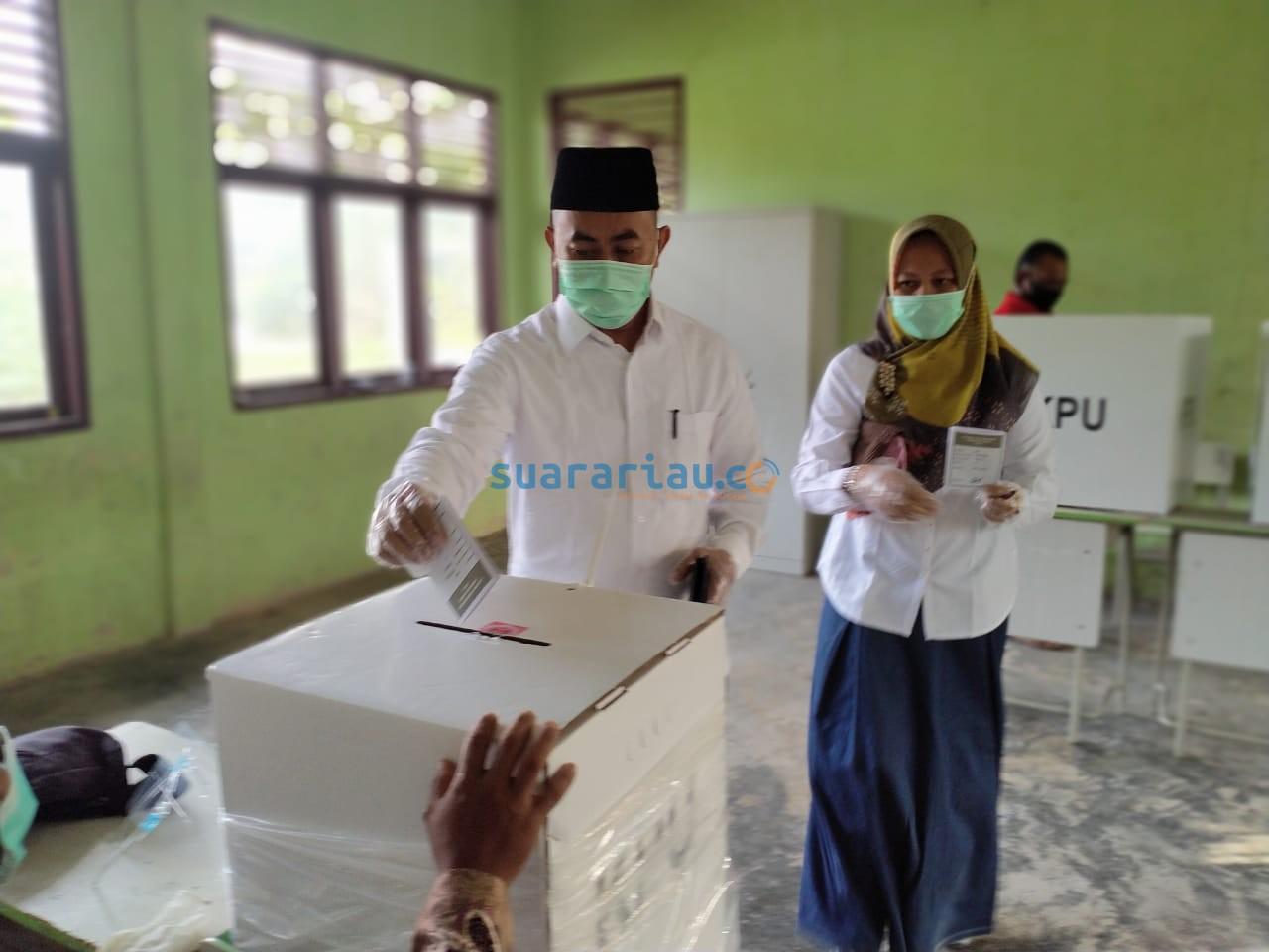 Calon Wakil Bupati Siak Sujarwo memasukkan surat suara ke kotak suara usai menggunakan hak pilih di TPS 1 Kampung Benteng Hilir