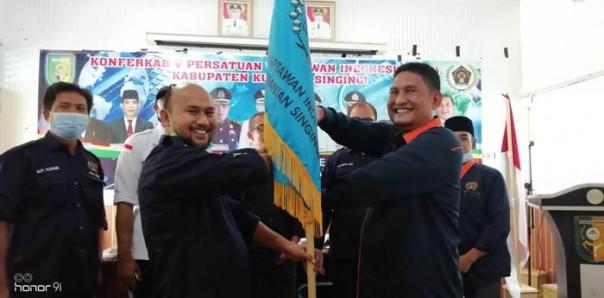 Sekretaris PWI Riau, Amril Jambak menyerahkan bendara pataka epada Ketua PQI KUansing terpilih, Ultra Sandi/ist