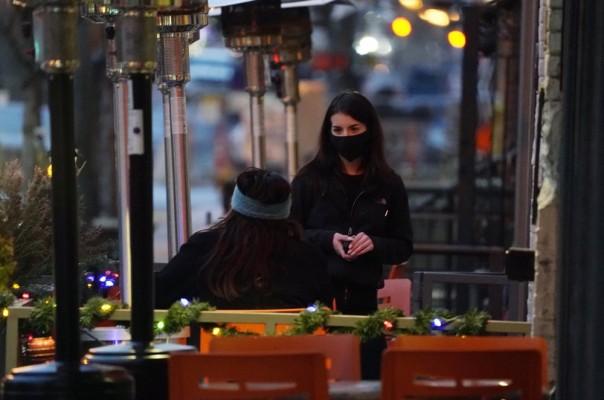 Seorang pramusaji mengenakan masker saat merawat pelindung yang duduk di teras luar sebuah restoran sushi, Senin malam, 28 Desember 2020, di pusat kota Denver. (Foto AP )