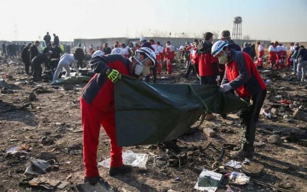 Dokumen foto Pekerja Bulan Sabit Merah memeriksa kantong plastik di lokasi kecelakaan pesawat Ukraine International Airlines setelah lepas landas dari bandara Imam Khomeini Iran, di pinggiran Teheran, Iran 8 Januari 2020. Nazanin Tabatabaee / WANA (Kantor Berita Asia Barat) via REUTERS