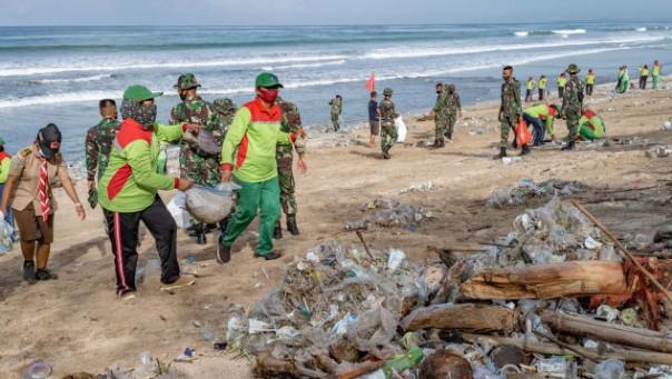 Pekerja membersihkan tumpukan puing dan sampah plastik yang dibawa oleh gelombang kuat di Pantai Kuta di Bali, Indonesia, pada 1 Januari 2021.(foto/cnn)
