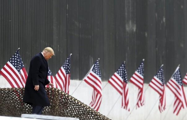 Presiden Donald Trump berjalan menuruni tangga sebelum pidato di dekat bagian tembok perbatasan AS-Meksiko, Selasa, 12 Januari 2021, di Alamo, Texas. (Foto/AP)