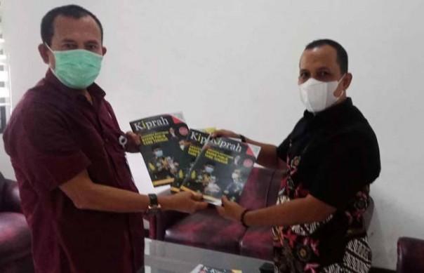 Ketua Komisi Informasi Riau Zufra Irwan menyerahkan buletin KI Riau kepada Kadis Kominfo Pers Inhil Trio Beni Putra./ist