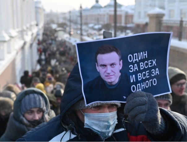 man holds a placard reading 'One for all, all for one' during a rally in Omsk [Alexey Malgavko/Reuters]